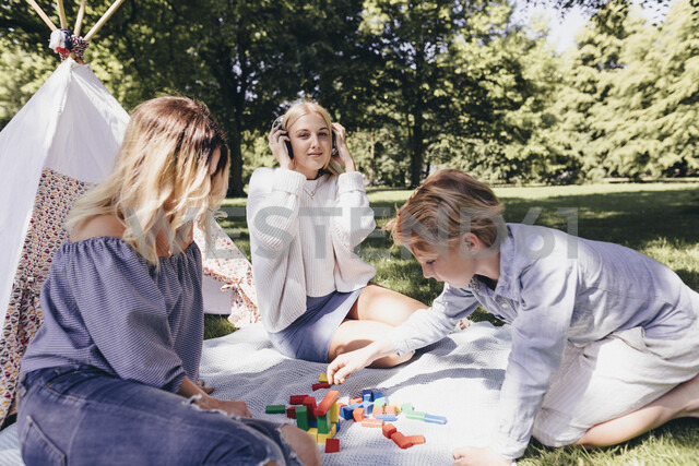 Two young women and a boy playing with building blocks in a park - KMKF00271