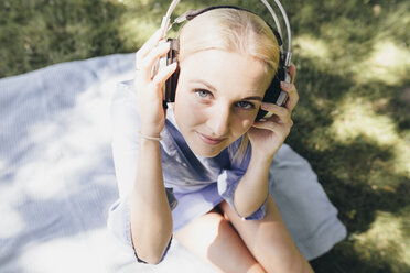 Portrait of smiling young woman sitting on blanket wearing headphones - KMKF00277