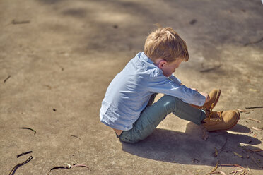 Boy sitting outdoors lacing his boots - BEF00160