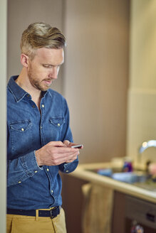 Man using cell phone at home - BEF00166