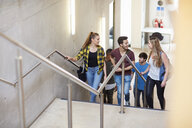 Group of students moving up stairway at higher education college - CUF22181