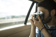 Young man on the road, taking photographs through car window - CUF22355