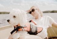 Coton de tulear dog sitting on woman's lap in boat, Orivesi, Finland - CUF22367