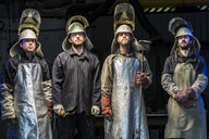 Portrait of four male foundry workers wearing protective clothing in bronze foundry - CUF22424