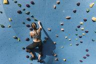 Young woman on climbing wall, Brooklyn Bridge Park, Brooklyn, New York, USA - ISF07992