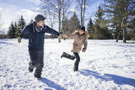 Young couple holding hands, running across snow covered field - ISF08001