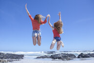 Girl and young woman jumping mid air on beach, Cape Town, South Africa - ISF08136