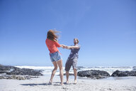 Young couple holding hands and spinning each other around on beach, Cape Town, South Africa - ISF08139