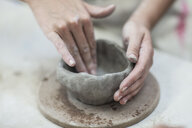 Hands of female potter shaping clay pot in workshop - ISF08157