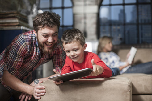 Father and son using digital tablet at home - ISF08178
