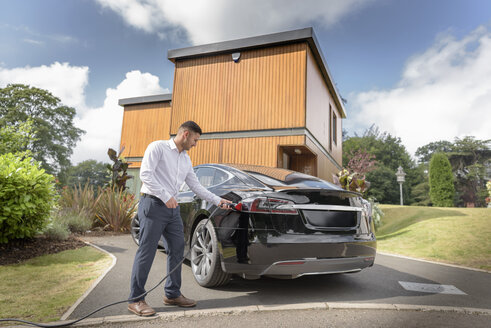 Man charging electric car outside modern house - CUF22634