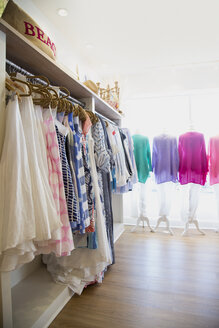 Rows of colorful dresses and blouses on clothes rail in fashion boutique - ISF08341
