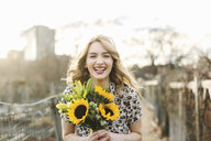 Portrait of young woman holding sunflowers, smiling - ISF08344