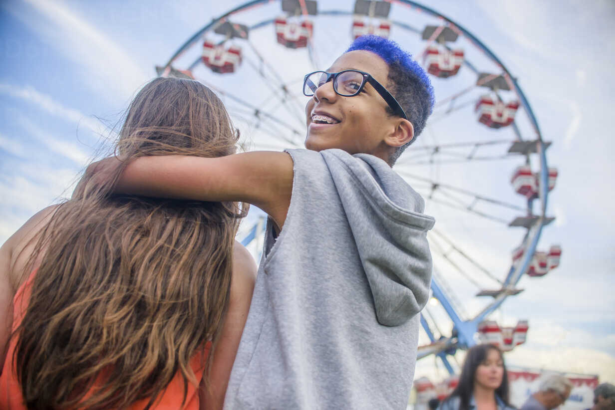 Rear View Of Teenage Couple Looking Over Shoulder In Front Of Ferris Wheel In Amusement Park