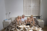 Grandmother in bed with grandsons using digital tablet - CUF22744