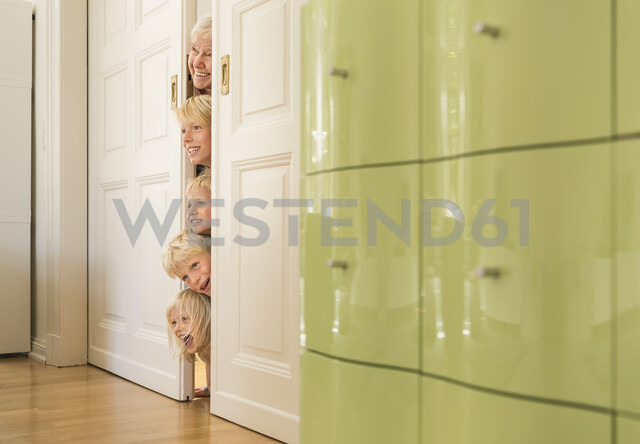 Grandmother and grandsons poking head through doorway - CUF22747
