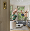 Boys in living room jumping in mid air - CUF22750