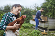 Young couple in chicken coop holding chicken - CUF22777