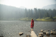 Woman wrapped in tartan blanket looking out over misty lake, Mount Hood National Forest, Oregon, USA - ISF08752