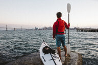 Man with kayak and oar, looking out to sea, San Francisco, California, USA - ISF08773