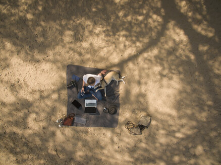 Bird's eye view of woman sitting on blanket with dog and laptop - ONF01116