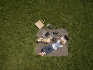 Bird's eye view of woman lying on blanket on meadow with dog using laptop - ONF01125