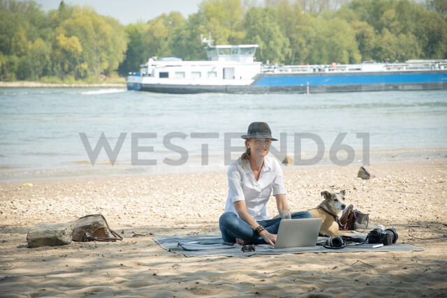 Smiling woman sitting on blanket at a river with dog using laptop - ONF01128 - noonland/Westend61