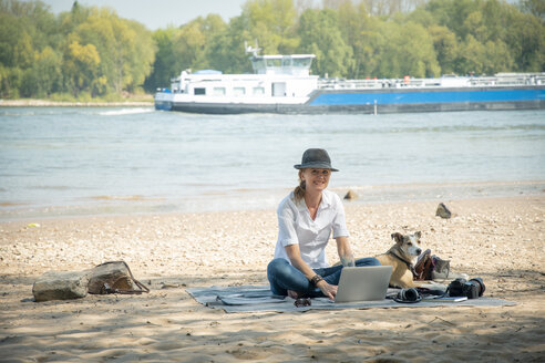 Smiling woman sitting on blanket at a river with dog using laptop - ONF01128