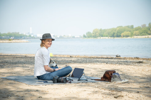 Smiling woman sitting on blanket at a river with dog and laptop - ONF01131