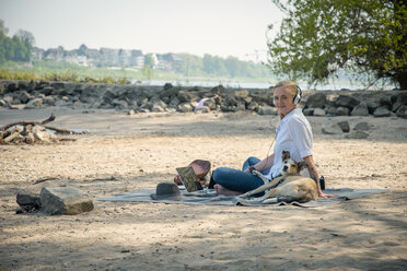 Smiling woman sitting on blanket at a river with dog wearing headphones - ONF01134