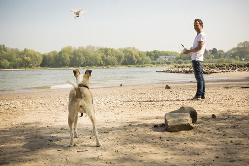 Man with a dog flying drone at a river - ONF01137
