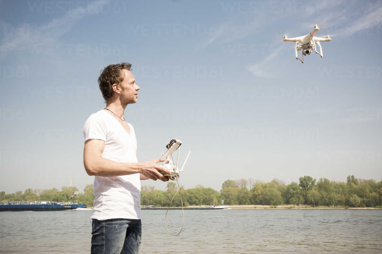 Man flying drone at a river - ONF01146 - noonland/Westend61