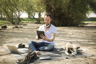 Man with dog sitting on blanket at a beach using tablet - ONF01152