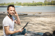 Portrait of smiling man sitting on blanket at a river using tablet - ONF01155