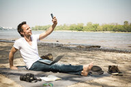 Smiling man sitting on blanket at a river taking a selfie - ONF01158
