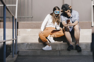Couple in disguise sitting on stairs, using smartphone - KNSF03919