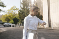 Young businesswoman carrying laptop, checking the time - KNSF03922