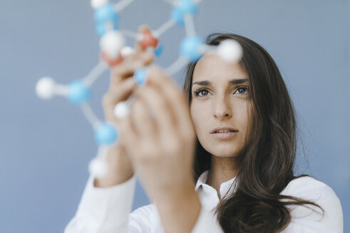 Female scientist holding molecule model, looking for solutions - KNSF03934