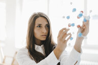 Female scientist holding molecule model, looking for solutions - KNSF03937