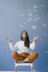 Pretty young woman playing with soap bubbles - KNSF03952
