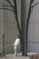 Young businesswoman leaning against atree in a backyard - KNSF03964