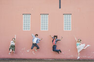 Friends jumping against pink wall background - CUF22823