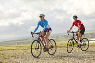 Cyclists riding on gravel road - CUF22877