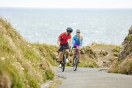 Cyclists riding on road overlooking ocean - CUF22880