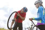 Cyclists fixing wheel on roadside - CUF22886
