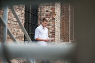 Young man using digital tablet beside brick building - CUF22937