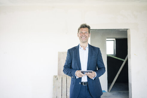 Portrait of smiling man in suit in building under construction - MOEF01231