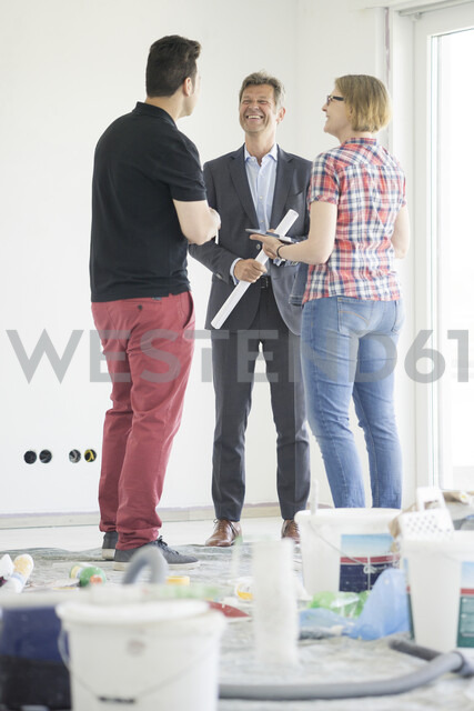 Smiling man in suit talking to couple in unfinished  building - MOEF01240 - Robijn Page/Westend61