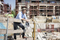 Smiling man holding hard hat on construction site looking around - MOEF01249