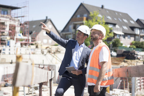 Man in suit talking to construction worker on construction site - MOEF01252